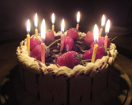 birthday cake with sweet strawberry and light candle in the dark photo