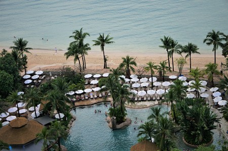Swimming pool garden with beach chairs and white umbrellas ,coconut trees beautiful near the beach and clear blue sea ,top view , Pattaya Thailand. Фото со стока