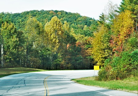 Curvy road to the Chattahoochee National forest park with fantastic colorful leaves changing in Fall season on the background of blue sky with white clouds, Autumn in North Georgia USA.