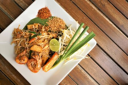 Shrimp Pad Thai is a popular Thai dish on the menu in all Thai restaurant, Top view, on the wooden background with copy space for text, Huahin Thailand. 스톡 콘텐츠