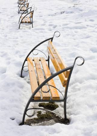 snowlandscape: Light brown wooden benches on snow