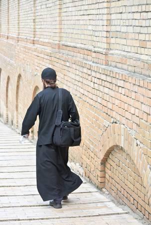 toog: Jonge ortodox monnik in zwarte soutane tegen de muur klooster (de Kiev-Pecherskaya Lavra-klooster, Kiev, Oekraïne)