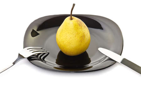 Fresh yellow pear on a black plate with fork and knife photo