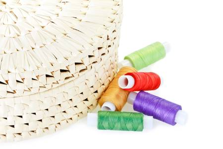 stitchwork: Handmade woven round box for stitchcraft with spools of thread isolated on white Stock Photo