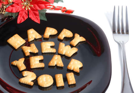 Black plate with character shaped cookies, fork and new year decoration isolated on white photo