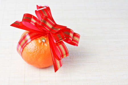 goldish: Ripe fresh orange tangerine with red goldish striped bow as a gift