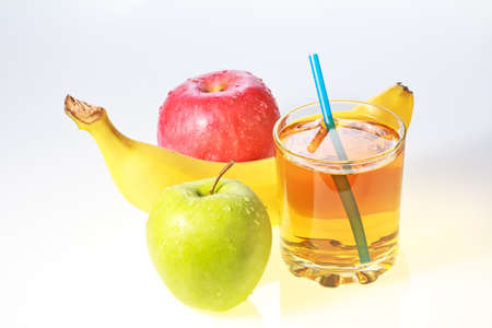 Banana, green and red apples and glass of apple juice with drinking straw  photo
