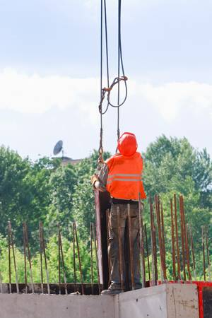 Rigger builder worker in orange uniform and helmet operating with straps at construction area photo