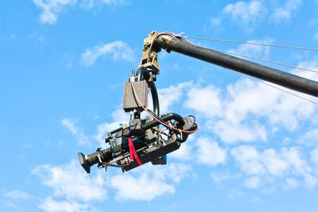 audiovisual: Professional tv camera on a crane in action against blue sky Stock Photo