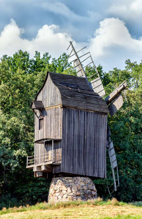 Old wooden traditional ukrainian windmill over blue sky with clouds photo