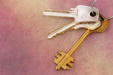 keyring: Three old house keys on keyring over grunge background