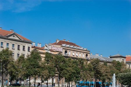 Old buildings on street of Zagreb. With skyline, trolley and statue on roof.