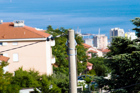 Electric pole with Adriatic sea and port of Rijeka in background Imagens