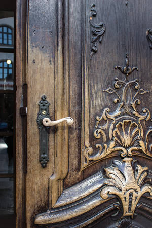 Detail of an old carved wooden door with metal handle