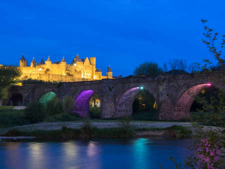 Blue hour photo overlooking the access bridge to the old fortified city of Carcassonne, lit in gold. France