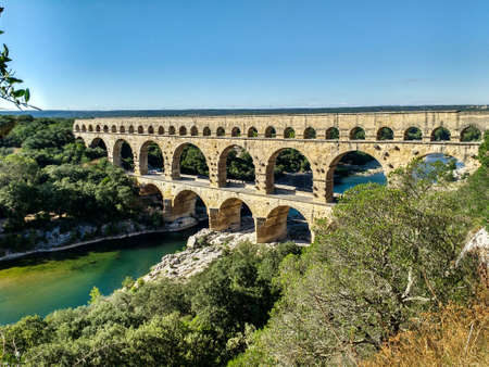 Three-tiered aqueduct Pont du Gard was built in Roman times on the river Gardon. Around the bridge is magnificent natural park. Provence, summer sunny day. Travel and holiday concept Banque d'images