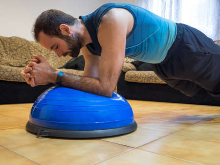 Muscular man doing bosu ball push-ups at home. Concept of sport.