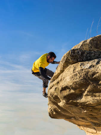 Man climbing a high rock in the mountains. Concept of adventure and extreme sport 版權商用圖片