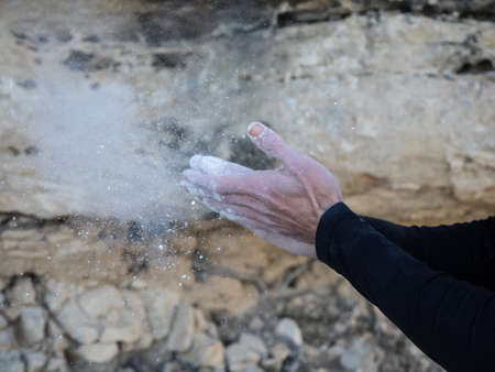 Climbing man covering his hands in magnesium powder chalk and preparing to climb outdoors. Concept of adventure and extreme sport