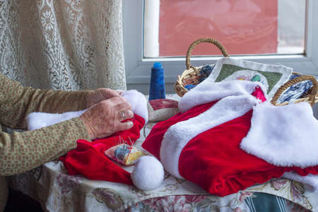 Mrs. Claus sewing the Santa suit for Christmas. Concept of Christmas. Copy space