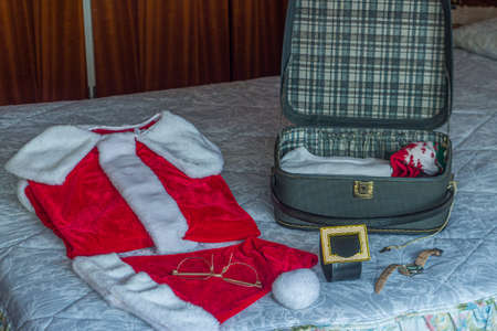 Preparing Santa's suitcase with his travel clothes. Selective approach. Concept of Christmas