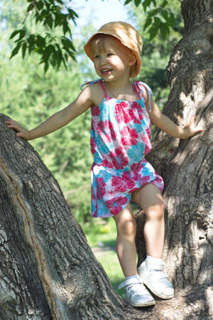 branching: Little girl in colored dress on a large branching tree Stock Photo