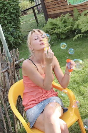 pacification: Young girl blowing bubbles in the summer on the nature