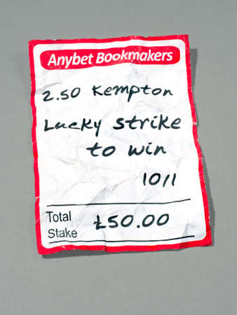 betting: Crumbled losing betting slip with shadow on plain background.