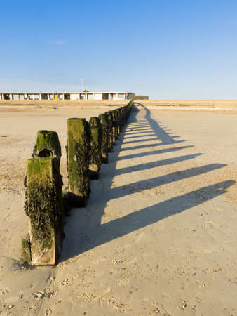 groyne: A groyne on Littlehampton, Sussex photographed looking towards the shore at low tide in Winter. Portrays the peace and solitude of the seaside out of season.