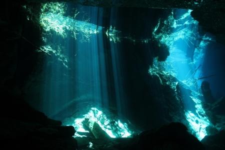 cueva: Rayos de sol que se rompe a través de la superficie en Cenote Chac Mool, Playa del Carmen, México