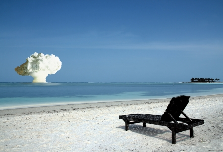 world war: Burnt up Sunbed on Tropical Island Beach, with Atomic Bomb in the Horizon Stock Photo
