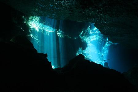 iluminados: Rayos de sol que se rompe a través de la superficie de Chac-Mool Cenote, Playa del Carmen, México