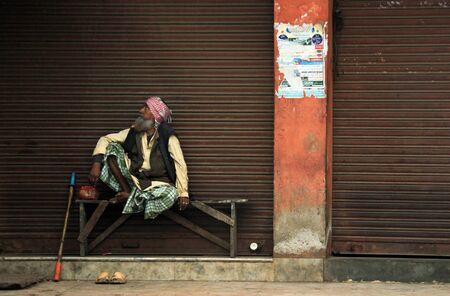 hombre pobre: Viejo hombre indio sentado en un banco, mirando de lado, Agra, India Editorial