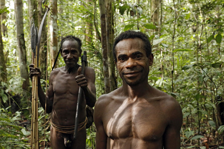 lowlands: Two Men of the Nomadic Forest Tribe Korowai, Standing in the Forest. Papua, Indonesia