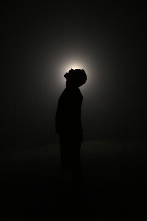Silhouette in the Dark, Head Leaning Backwards with Open Mouth. Light behind Head.