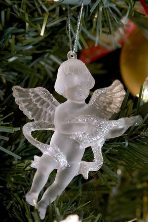 Crystal angel christmas decorations on silver light.