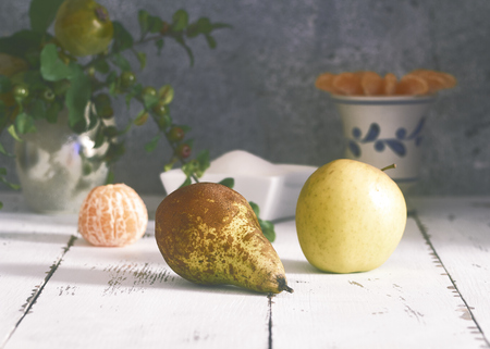 pear, apple and clementine on white rustic table with ornaments and gray background Imagens