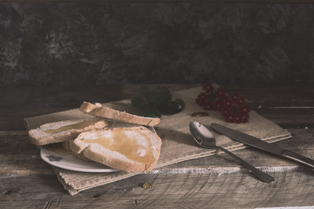 slices of bread with honey on white plate with decorations on rustic table