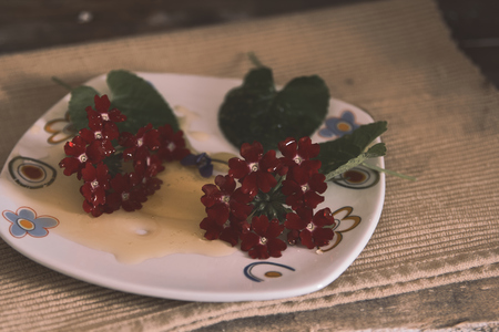 flowers dipped with honey on a white plate with ornaments that is on a wooden table