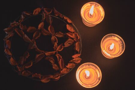 pentacle made with dry reddish leaves and three burning candles on black background Stock Photo