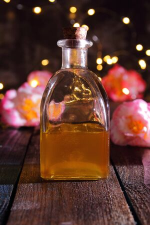 a glass jar with camellia oil and some camellia flowers