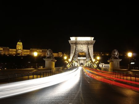 Chain bridge at night time with cars. Stock Photo