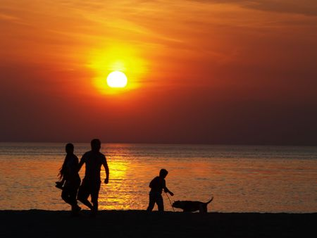 Family at the beach at sunset photo