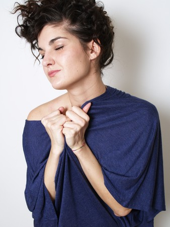 Young woman in blue t-shirt hugging herself