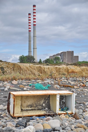 Trashed fridge on the seashore next to a factory photo
