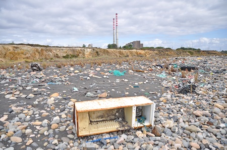 trashed: Trashed fridge on the seashore next to a factory Editorial