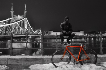 Cyclist sitting next to his red bike at Budapest