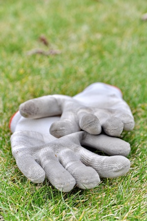 gardening gloves: Dirty gardening gloves on the grass Stock Photo