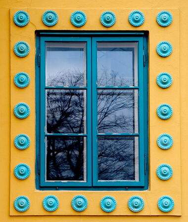 colored window: Cyan colored window on a yellow wall Stock Photo