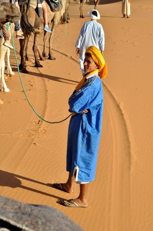 merzouga: MERZOUGA DESERT - OCTOBER 01  Man in traditional Berber wear, walking in Merzouga Desert, Morocco on October 01, 2013